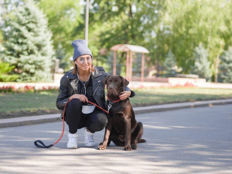 Uma menina abraça seu cão ao squatting um cão fotografia de stock royalty free