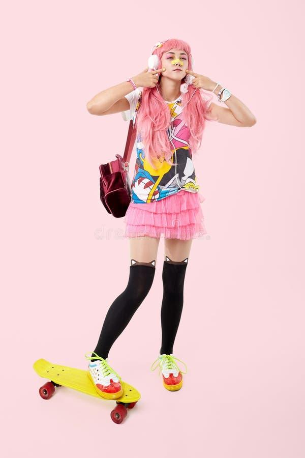Uma menina adolescente asiática bonita nos fones de ouvido cor-de-rosa, vestidos no anime imagens de stock royalty free