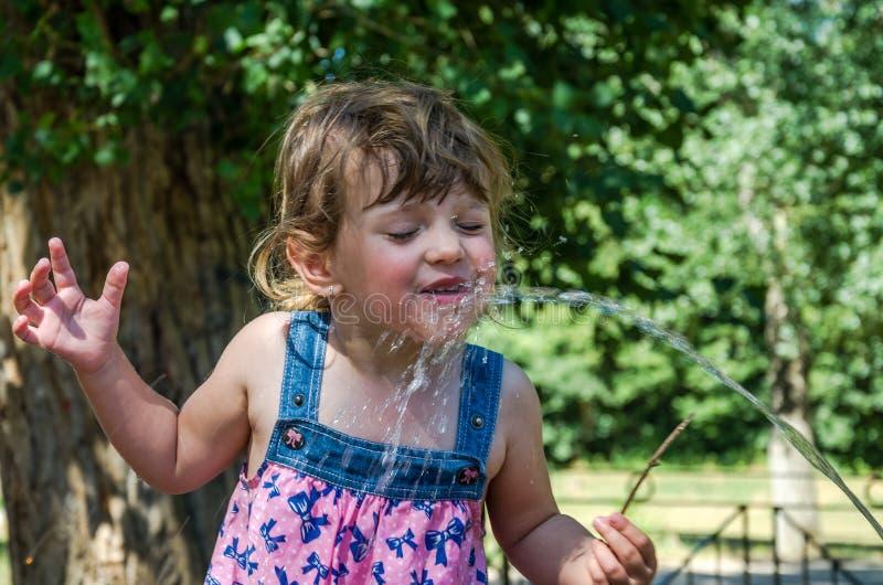 Uma menina adorável pequena, um bebê em um vestido, bebidas molha de um bico de uma fonte bebendo romana em um dia de verão quent foto de stock royalty free