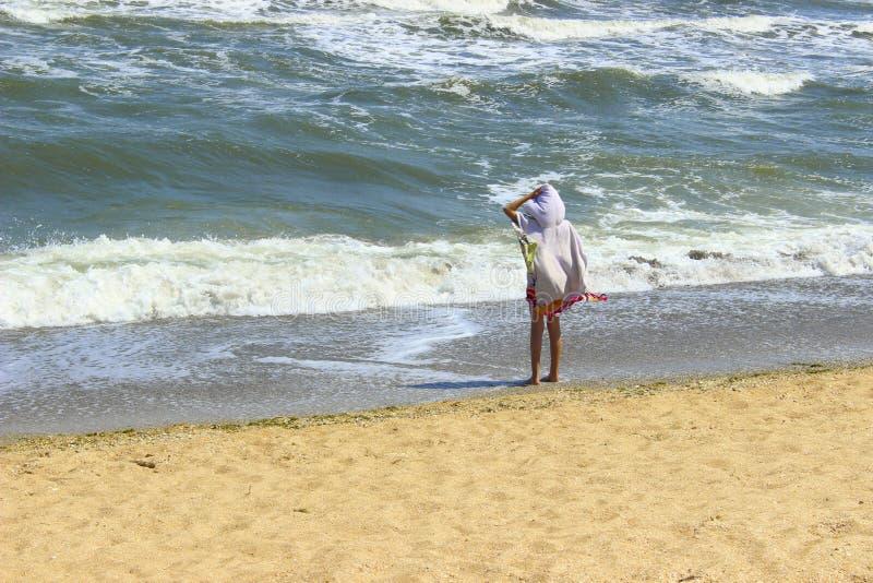 Uma menina adorável que aprecia na praia Moça que olha a opinião de acalmação da praia fotos de stock