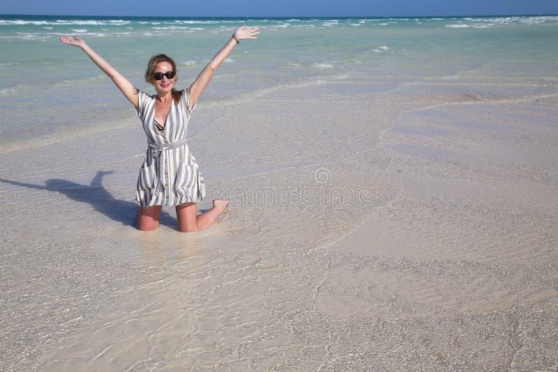 Uma menina adulta ajoelha-se no mar, braços estendidos imagem de stock royalty free