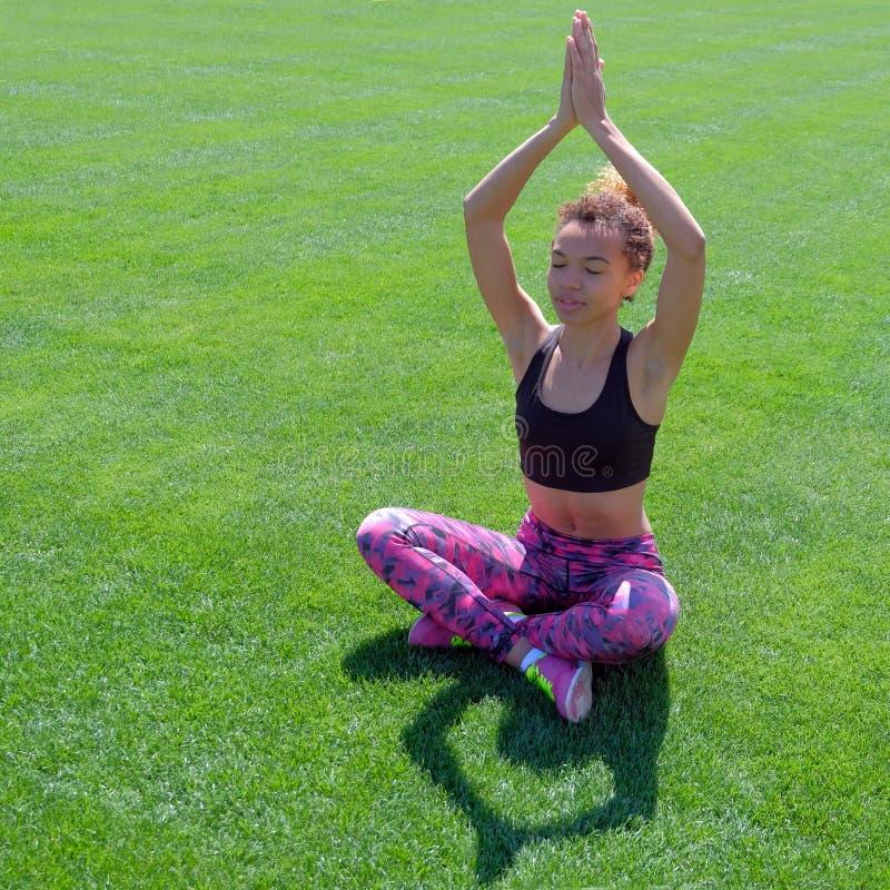 Uma menina afro-americano no verão na roupa dos esportes levantou suas mãos acima e medita Menina preta bonito nova que senta-se  fotografia de stock