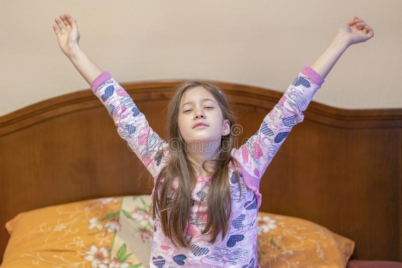 Uma menina agradável da criança aprecia a manhã ensolarada Bom dia em casa A menina da criança acorda do sono Menina que estica n imagem de stock royalty free