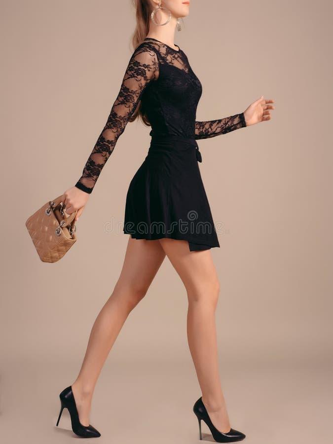 Uma menina alta, delgada em pouco vestido preto com as bolsas curtos da forma toma uma etapa fotografia de stock royalty free