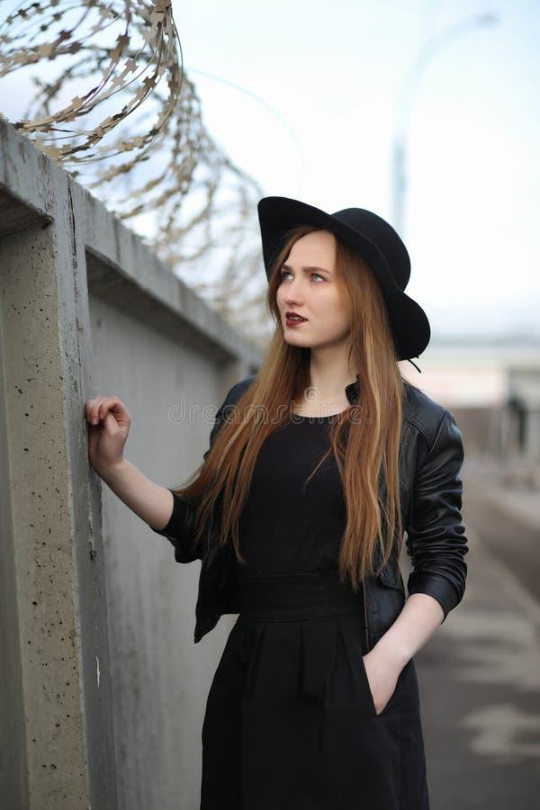 Uma menina anda abaixo da rua da cidade em um waistcoat de couro com a fotos de stock royalty free