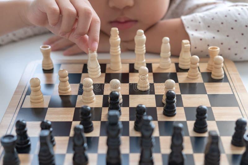 Uma menina aprende como jogar o jogo de xadrez fotografia de stock royalty free