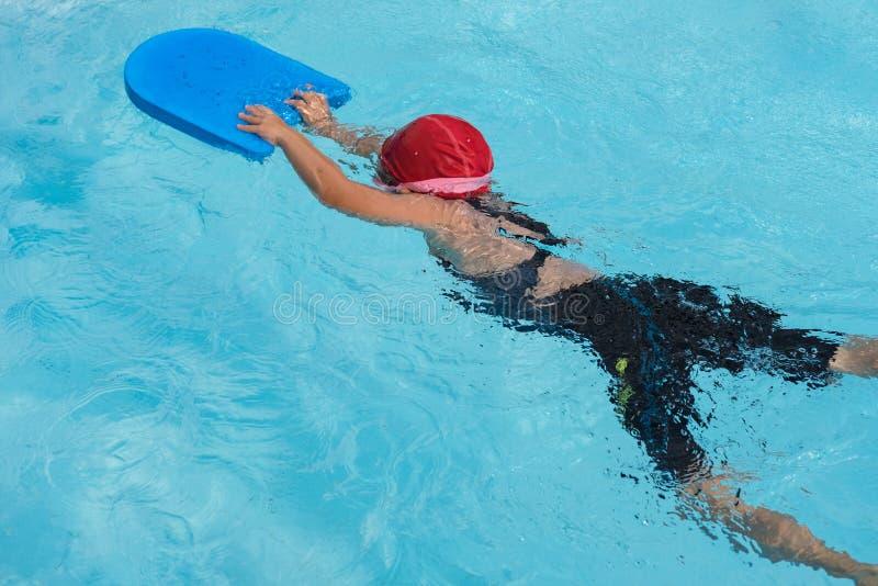 Uma menina aprende como nadar na classe da nata??o imagens de stock