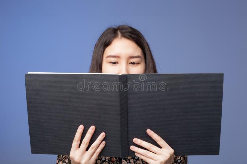 Uma menina asiática em um vestido que lê um livro negro em suas mãos imagens de stock royalty free
