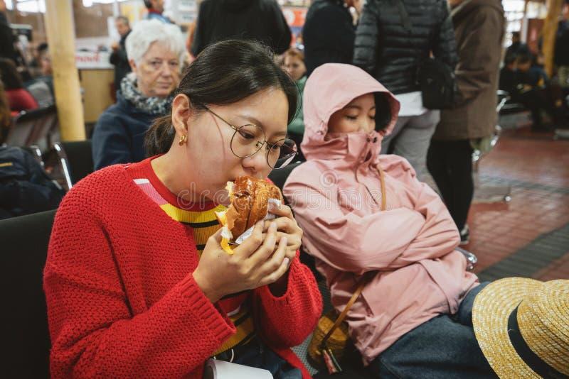Uma menina asiática está comendo uma Hamburgo para o café da manhã em Maria Reiche Neuman Airport no Peru E seu amigo olham muito imagens de stock