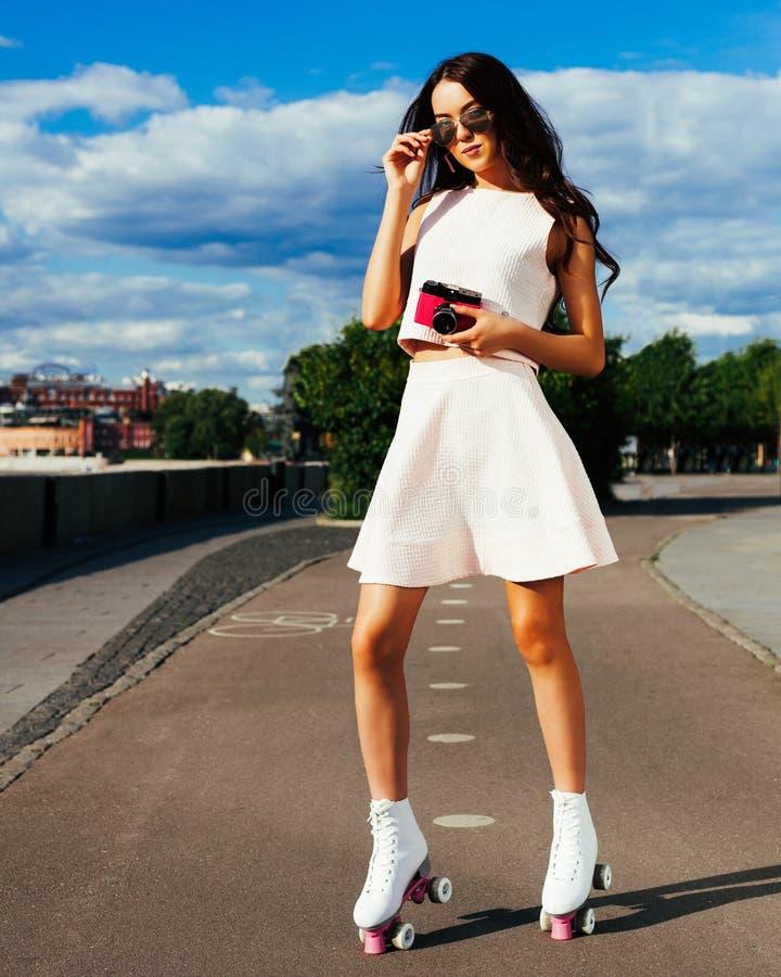 Uma menina asiática incrível nos óculos de sol e um equipamento brilhante do verão que levanta em patins de rolo com uma câmera c imagens de stock