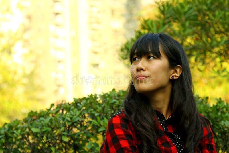 Uma menina asiática que esteja pensando imagem de stock