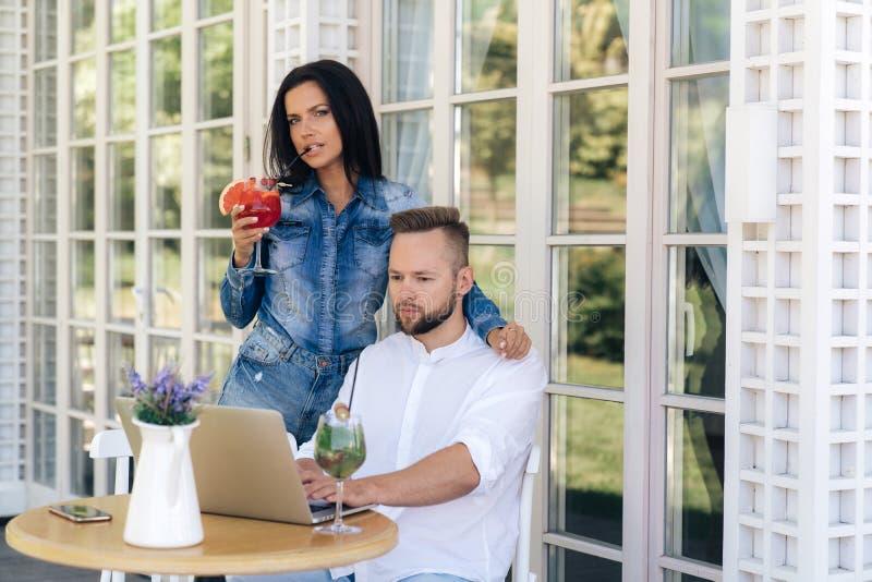 Uma menina atrativa abraça seu noivo no café, bebe um cocktail delicioso Um homem autônomo é ocupado trabalhar na foto de stock