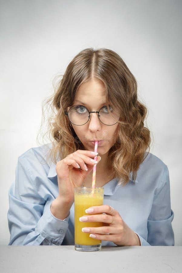 Uma menina bebe o suco de laranja foto de stock royalty free