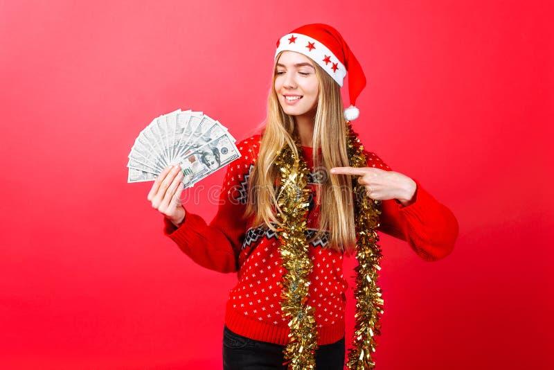 Uma menina bem sucedida em uma camiseta e em um chapéu vermelhos de Santa guarda o dinheiro em um fundo vermelho e aponta seu ded imagem de stock