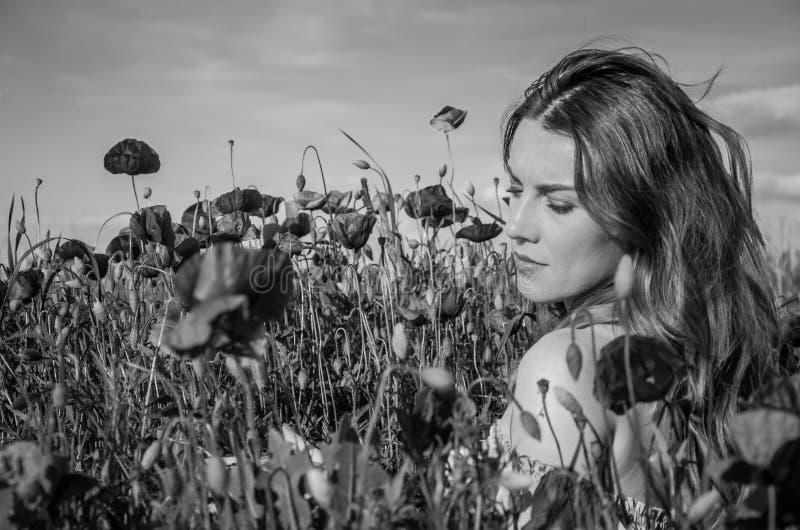 Uma menina bonita alegre nova anda em um prado da papoila entre papoilas de florescência do vermelho em um dia de verão brilhante fotografia de stock royalty free