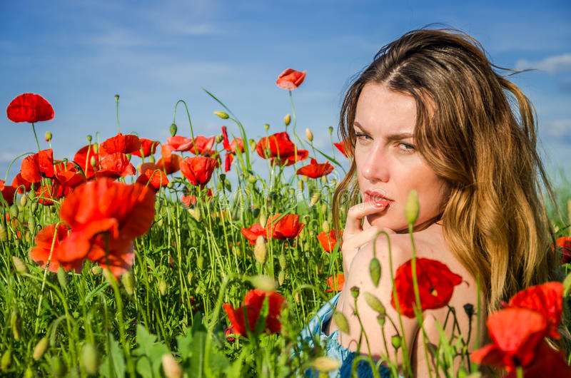 Uma menina bonita alegre nova anda em um prado da papoila entre papoilas de florescência do vermelho em um dia de verão brilhante fotos de stock royalty free