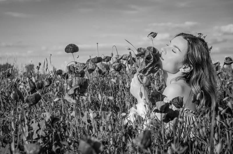 Uma menina bonita alegre nova anda em um prado da papoila entre papoilas de florescência do vermelho em um dia de verão brilhante imagem de stock
