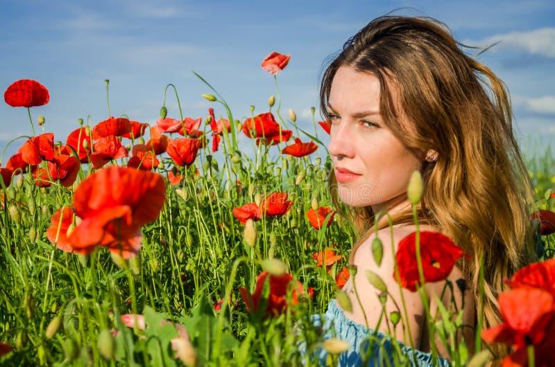 Uma menina bonita alegre nova anda em um prado da papoila entre papoilas de florescência do vermelho em um dia de verão brilhante foto de stock royalty free