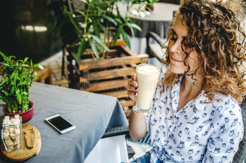 Uma menina bonita com cabelo encaracolado aprecia um latte delicioso em um café imagem de stock royalty free
