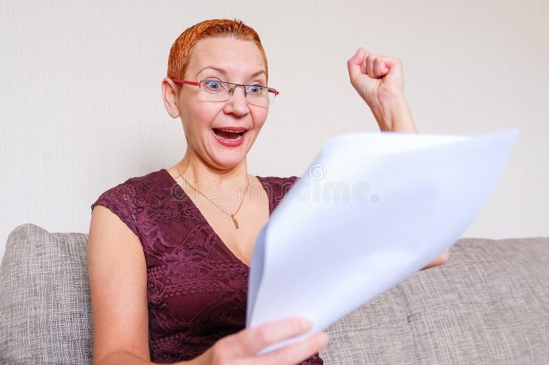 Uma menina bonita com vidros com um quadro vermelho leu a notícia positiva nos documentos Emoções da alegria com o gesto da imagens de stock