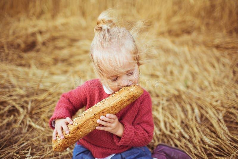 Uma menina bonita come um pão em um campo imagem de stock royalty free