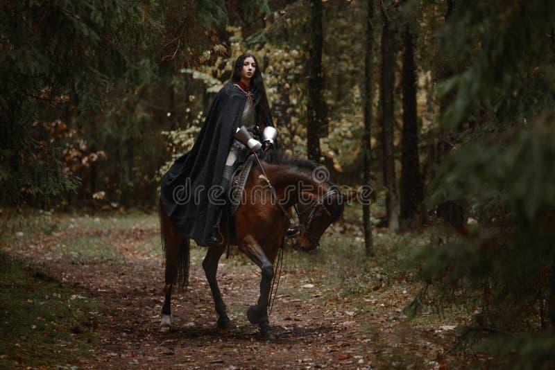 Uma menina bonita do guerreiro com um chainmail e uma armadura vestindo da espada que montam um cavalo em uma floresta misteriosa imagens de stock