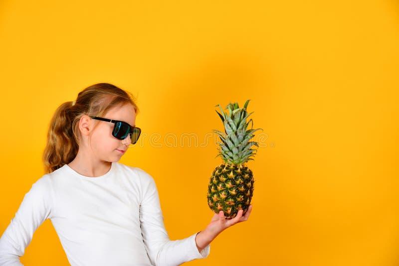 Uma menina bonita e bonito nos óculos de sol guarda um abacaxi e olha-o, em um fundo amarelo no estúdio foto de stock royalty free