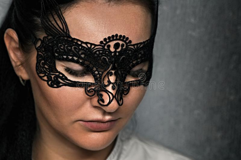 Uma menina bonita em uma máscara a céu aberto do carnaval com chicotes chiques imagem de stock royalty free
