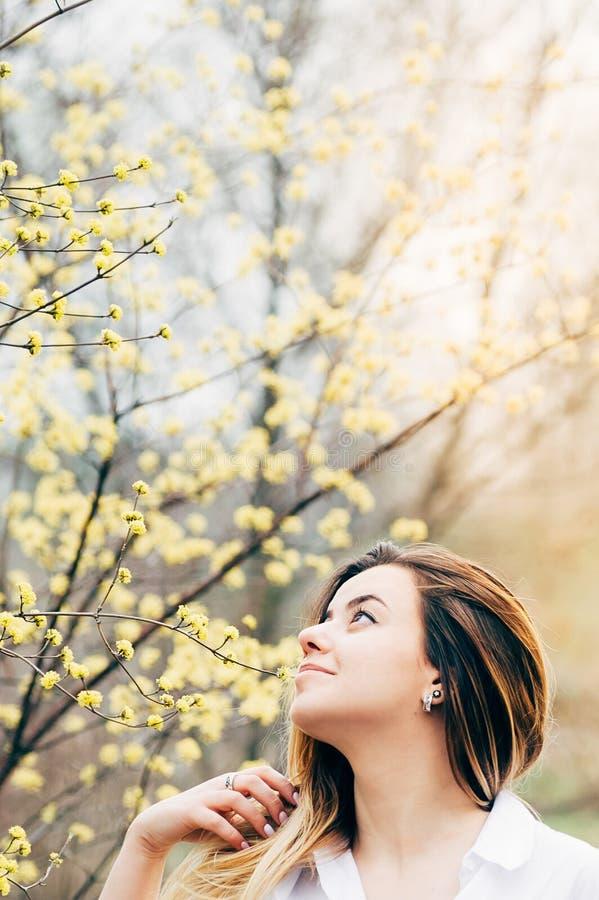 Uma menina bonita em um jardim aprecia árvores de florescência imagens de stock royalty free