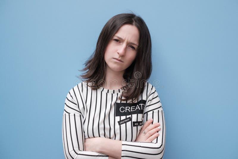 Uma menina bonita em um t-shirt listrado está estando pela parede azul foto de stock royalty free