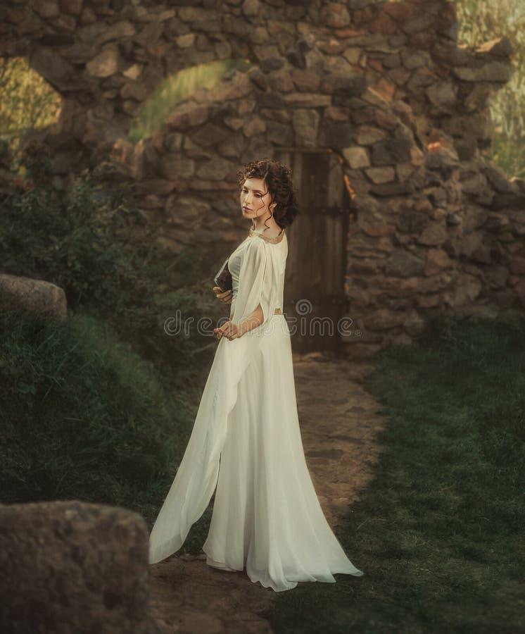 Uma menina bonita em um vestido branco do vintage fotografia de stock