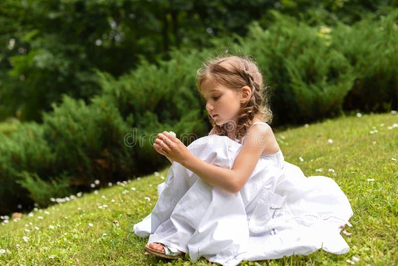 Uma menina bonita em um vestido longo branco que senta-se na grama e na vista verde-clara fotografia de stock royalty free
