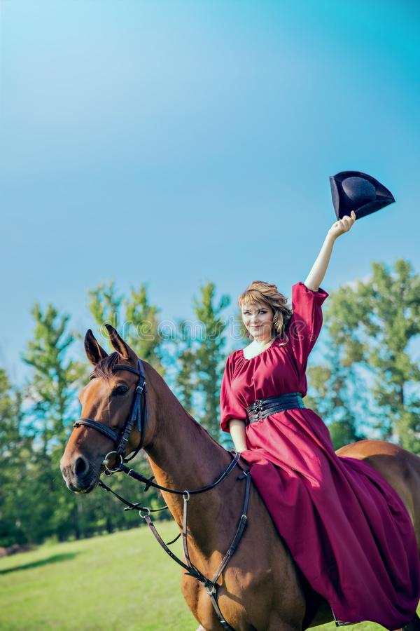 Uma menina bonita em um vestido vermelho longo monta um cavalo e sacode seu chapéu imagem de stock royalty free