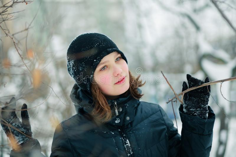 Uma menina bonita espalhou os ramos de uma árvore foto de stock royalty free