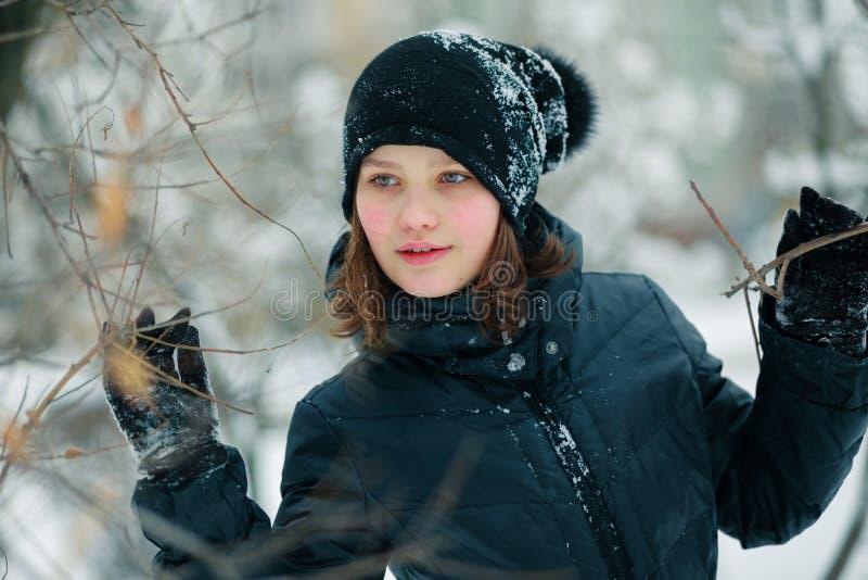 Uma menina bonita espalhou os ramos de uma árvore fotos de stock