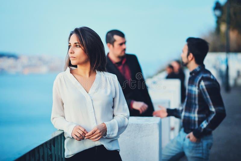 Uma menina bonita está em uma ponte no por do sol e olha na distância contra um céu azul e uma cidade da noite Uma jovem mulher d fotografia de stock