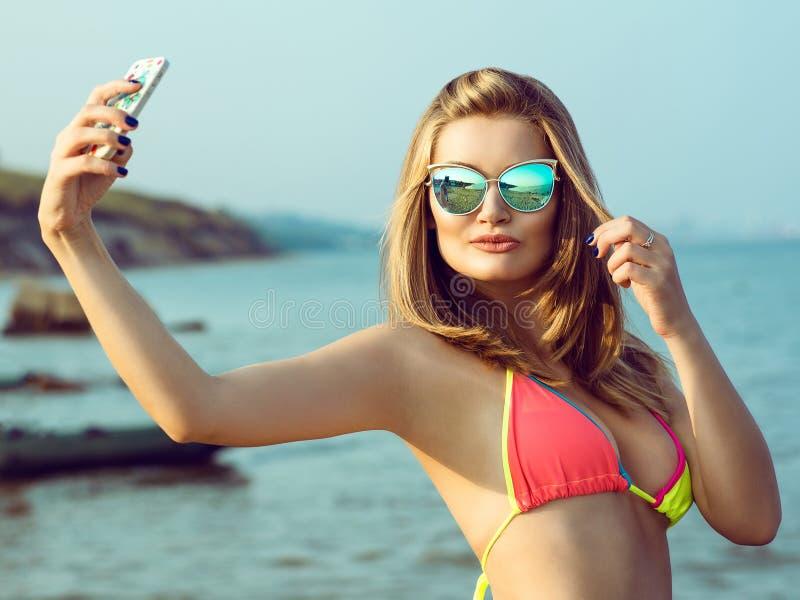 Uma menina bonita nos óculos de sol e no roupa de banho está fazendo o selfie na praia fotos de stock royalty free