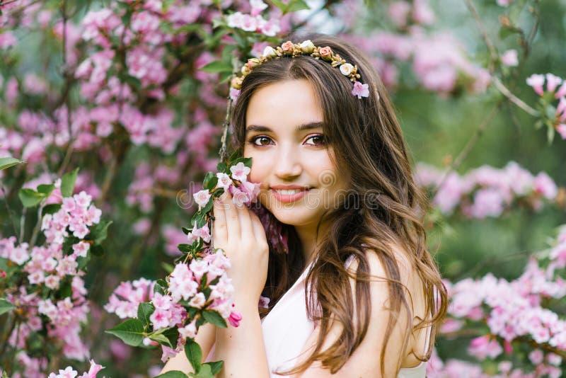 Uma menina bonita nova bonita com cabelo longo está frouxamente perto da mola de florescência Bush do weigela com flores cor-de-r fotos de stock