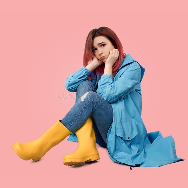 Uma menina bonita nova em um revestimento azul e em umas botas de borracha amarelas senta-se com uma expressão triste e triste em imagens de stock royalty free
