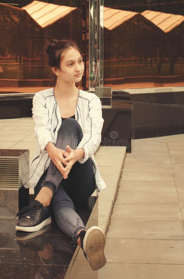 Uma menina bonita nova está sentando-se na rua Foto matizada imagens de stock royalty free