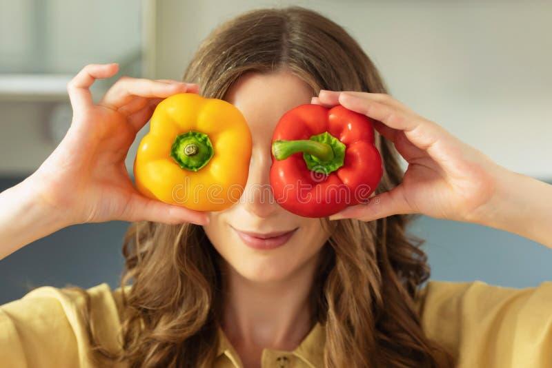 Uma menina bonita nova guarda uma pimenta doce em suas mãos, tem o divertimento e fecha seus olhos fotos de stock
