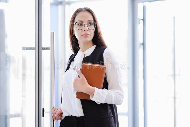 Uma menina bonita nova nos monóculos entra na porta de vidro do escritório foto de stock royalty free