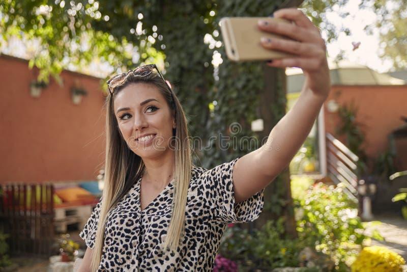 Uma menina bonita nova que toma um instantâneo, fotografando ela mesma, selfie, no jardim do café exterior, usando o smartphone imagem de stock royalty free