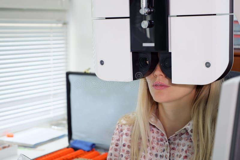 Uma menina bonita os olhos testa na clínica imagens de stock