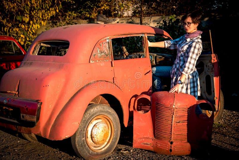 Uma menina bonita que levanta em torno de um carro retro vermelho velho jogado imagens de stock