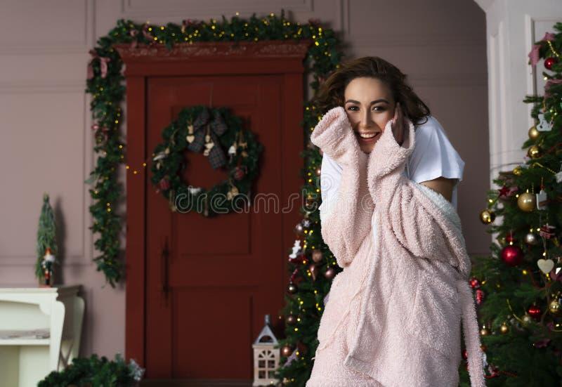 Uma menina bonita que veste um roupão macio morno é sorrir seguinte foto de stock