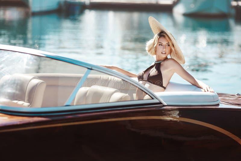 Uma menina bonita, um modelo em um roupa de banho e um chapéu largo-brimmed imagem de stock royalty free