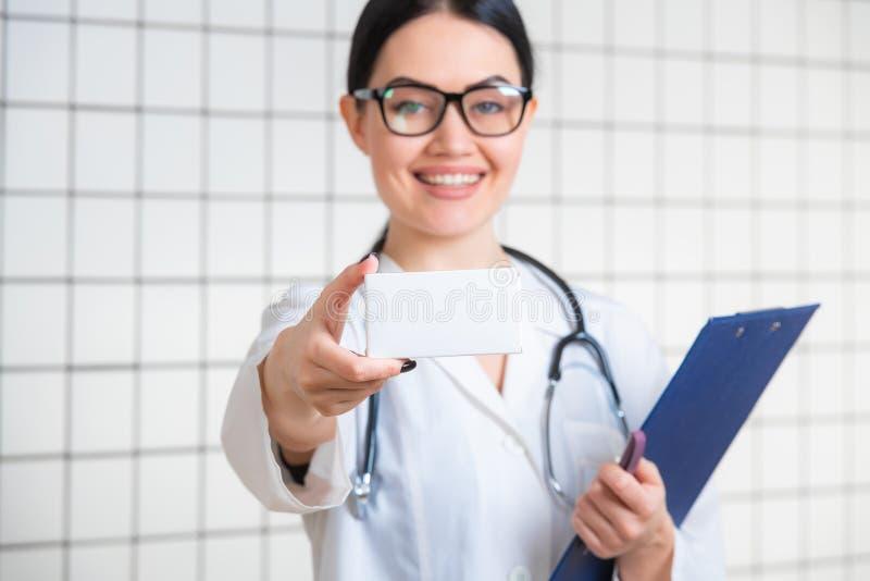 Uma menina bonito amigável com cabelo escuro e vidros, vestindo um revestimento do laboratório, lê com cuidado a informação no bl fotografia de stock