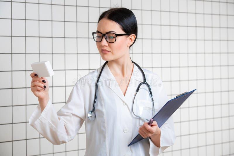 Uma menina bonito amigável com cabelo escuro e vidros, vestindo um revestimento do laboratório, lê com cuidado a informação no bl fotos de stock