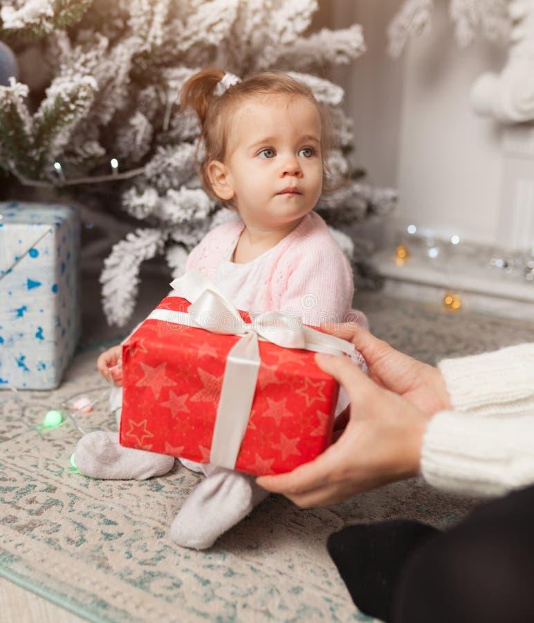 Uma menina bonito bonita abre um presente de ano novo Com a árvore de Natal no fundo imagem de stock